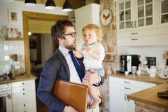 Homme d'affaires venant à la maison, tenant le petit fils dans les bras Photo libre de droits