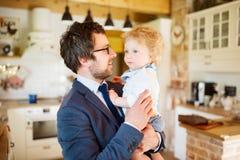 Homme d'affaires venant à la maison, tenant le petit fils dans les bras Images libres de droits