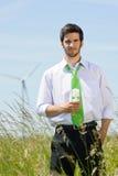 Homme d'affaires vert d'énergie dans l'ampoule de prise de zone Photographie stock