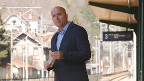 Homme d'affaires Waiting Train Arrivals dans une station de train photographie stock