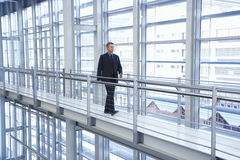Homme d'affaires Walking By Railing dans le bureau moderne Photographie stock