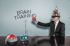 Homme d'affaires Wearing Helmet Holding Brain While Sitting By Text images stock