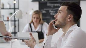 Homme d'affaires Working et parler au téléphone pour le plan réussi dans le bureau créatif