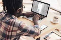 homme d'afro-américain à l'aide de l'ordinateur portable avec le site Web et le smartphone de linkedin photo stock