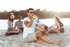 Homme d'afro-américain dans des lunettes de soleil buvant de la bière tandis que ses amis se reposant derrière sur la plage sablo Photographie stock