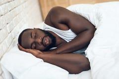 Homme d'afro-américain dormant dans le lit photos stock