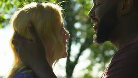 Homme d'afro-américain embrassant et étreignant sa femme blonde avec la tendresse banque de vidéos