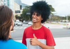 Homme d'afro-américain montrant le pouce à un ami caucasien Image libre de droits