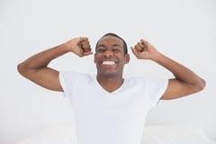 Homme d'Afro se réveillant dans le lit et étirant ses bras Images libres de droits