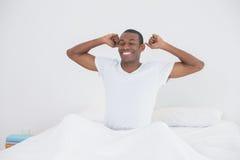 Homme d'Afro se réveillant dans le lit et étirant ses bras Images stock