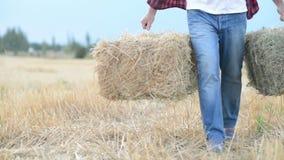 Homme d'agriculteur avec des balles de paille banque de vidéos