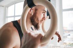 Homme d'ajustement détendant sur des anneaux de gymnastique après séance d'entraînement intense images libres de droits