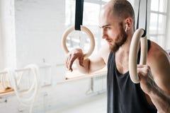 Homme d'ajustement détendant sur des anneaux de gymnastique après séance d'entraînement intense image stock