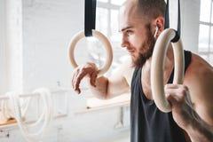 Homme d'ajustement détendant sur des anneaux de gymnastique après séance d'entraînement intense photo stock