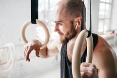 Homme d'ajustement détendant sur des anneaux de gymnastique après séance d'entraînement intense photographie stock libre de droits
