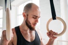 Homme d'ajustement détendant sur des anneaux de gymnastique après séance d'entraînement intense photos stock