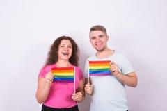Homme d'amusement et femme se tenant avec des drapeaux d'arc-en-ciel, concept de lgbt Photos libres de droits