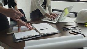 Homme d'architecte travaillant avec l'ordinateur portable et les modèles, inspection d'ingénieur dans le lieu de travail pour le  banque de vidéos