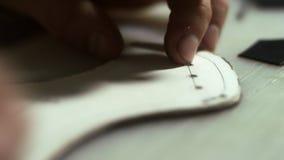 Homme d'artisan faisant des trous Fermez-vous vers le haut des mains en cuir d'artisan fonctionnant avec le cuir banque de vidéos