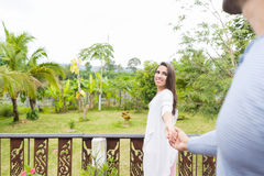Homme d'avance de femme tenant la main sur la terrasse d'été avec couples de sourire heureux de beau paysage en bois vert de jeun Photo libre de droits