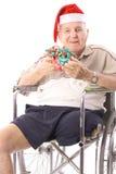 Homme d'Eldery dans le fauteuil roulant célébrant le ver de Noël Photo libre de droits