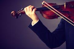 Homme d'homme habillé d'une manière élégante jouant le violon Photos libres de droits