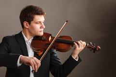 Homme d'homme habillé d'une manière élégante jouant le violon images libres de droits