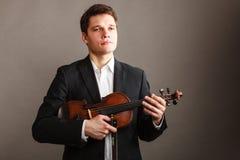 Homme d'homme habillé d'une manière élégante tenant le violon Photographie stock libre de droits