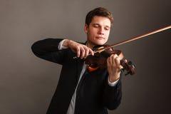 Homme d'homme habillé d'une manière élégante jouant le violon photographie stock libre de droits