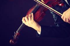 Homme d'homme habillé d'une manière élégante jouant le violon photo libre de droits