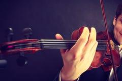 Homme d'homme habillé d'une manière élégante jouant le violon photos stock