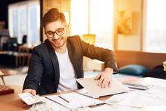 Homme d'indépendant comptant l'ordinateur portable fermant d'argent se reposant au bureau Images stock