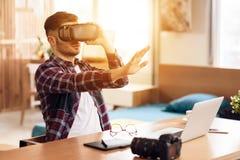 Homme d'indépendant employant la réalité virtuelle à l'ordinateur portable se reposant au bureau image stock