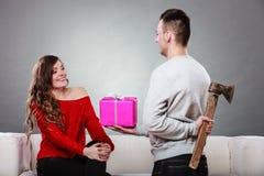 Homme d'Insincire tenant la hache donnant le boîte-cadeau à la femme images libres de droits