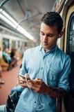 Homme d'intoxiqué de téléphone à l'aide de l'instrument dans la métro photo stock