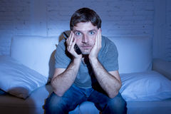 Homme d'intoxiqué de télévision à la maison se trouvant sur le divan regardant la TV juger à télécommande images stock