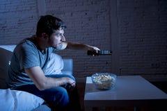 Homme d'intoxiqué de télévision s'asseyant sur le sofa à la maison regardant la TV manger du maïs éclaté utilisant à télécommande Image libre de droits