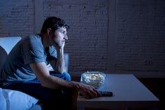 Homme d'intoxiqué de télévision s'asseyant sur le sofa regardant la TV manger du maïs éclaté utilisant le regard à télécommande e images stock