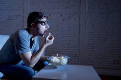 Homme d'intoxiqué de télévision sur le sofa regardant la TV et mangeant du maïs éclaté en verres drôles de connaisseur de ballot photo libre de droits