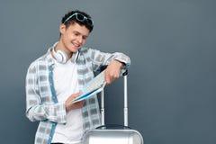 Homme d'isolement sur la position grise de concept de tourisme de mur avec la valise choisissant la destination sur la carte gaie photos stock