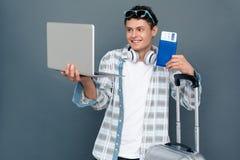Homme d'isolement sur le concept gris de tourisme de mur se tenant avec le bagage ayant le faire appel visuel au passeport d'appa photo libre de droits