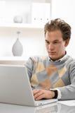 homme d'ordinateur portatif utilisant des jeunes Image stock