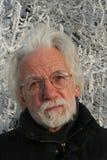 Homme d'une chevelure blanc sur le fond d'arbre d'hiver Photos stock