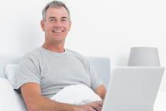 Homme d'une chevelure gris heureux à l'aide de son ordinateur portable dans le lit Photo stock