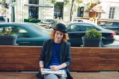 Homme d'une chevelure rouge de hippie s'asseyant sur le banc avec le journal Images stock