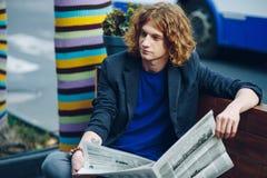 Homme d'une chevelure rouge de hippie s'asseyant sur le banc avec le journal Image libre de droits