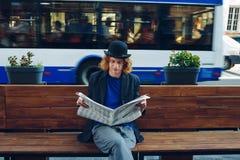 Homme d'une chevelure rouge de hippie s'asseyant sur le banc avec le journal Photos libres de droits