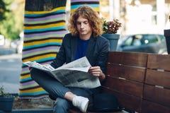 Homme d'une chevelure rouge de hippie s'asseyant sur le banc lisant un journal Photographie stock
