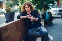 Homme d'une chevelure rouge de hippie s'asseyant sur le banc regardant à sa montre Images libres de droits