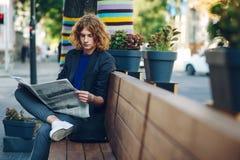 Homme d'une chevelure rouge de hippie s'asseyant sur le journal de lecture de banc Photographie stock libre de droits